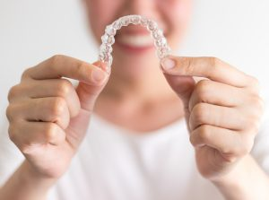 Smiling woman holding Invisalign aligners