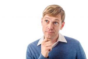 man holding chin pondering decision