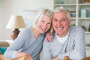 elderly couple in gray sweaters smiling with dental implants in Florham Park